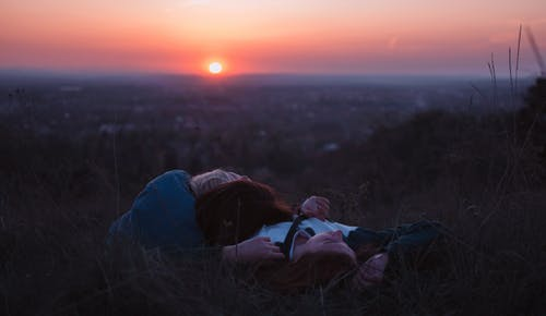 People Lying on Green Grass during Sunset