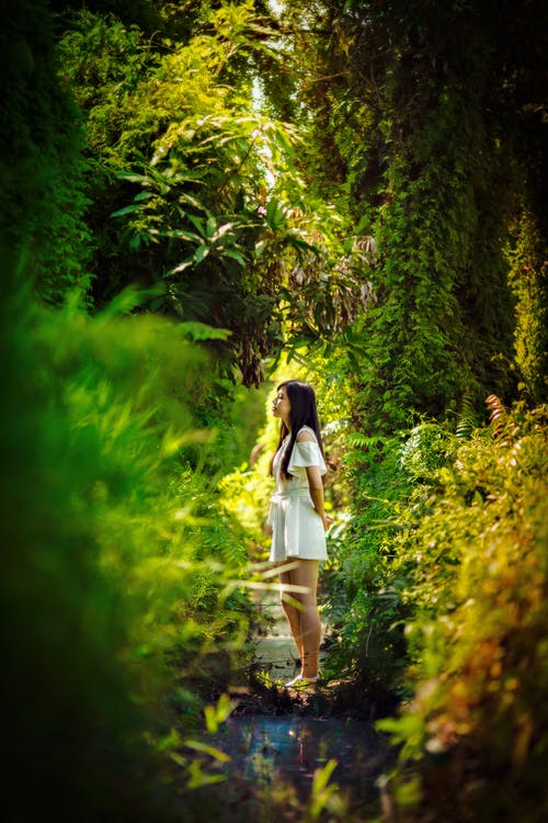 Young woman standing in green garden