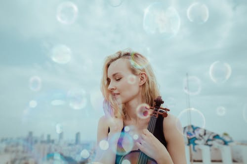 Tranquil young woman resting on roof with violin against blurred cityscape