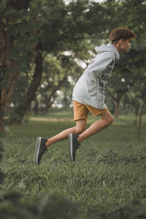Man in Gray Hoodie Jumping on the Grass