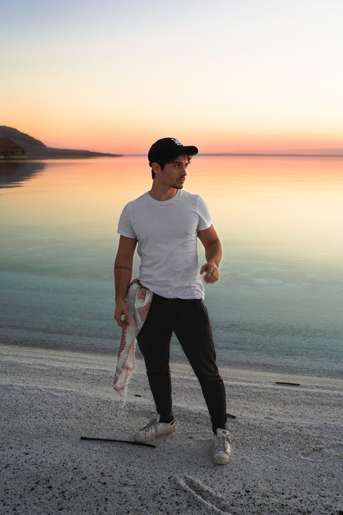 Calm young man relaxing on sandy beach during sundown