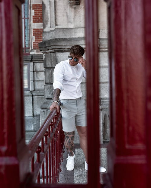 Young stylish male tourist leaning on railing on balcony of aged building