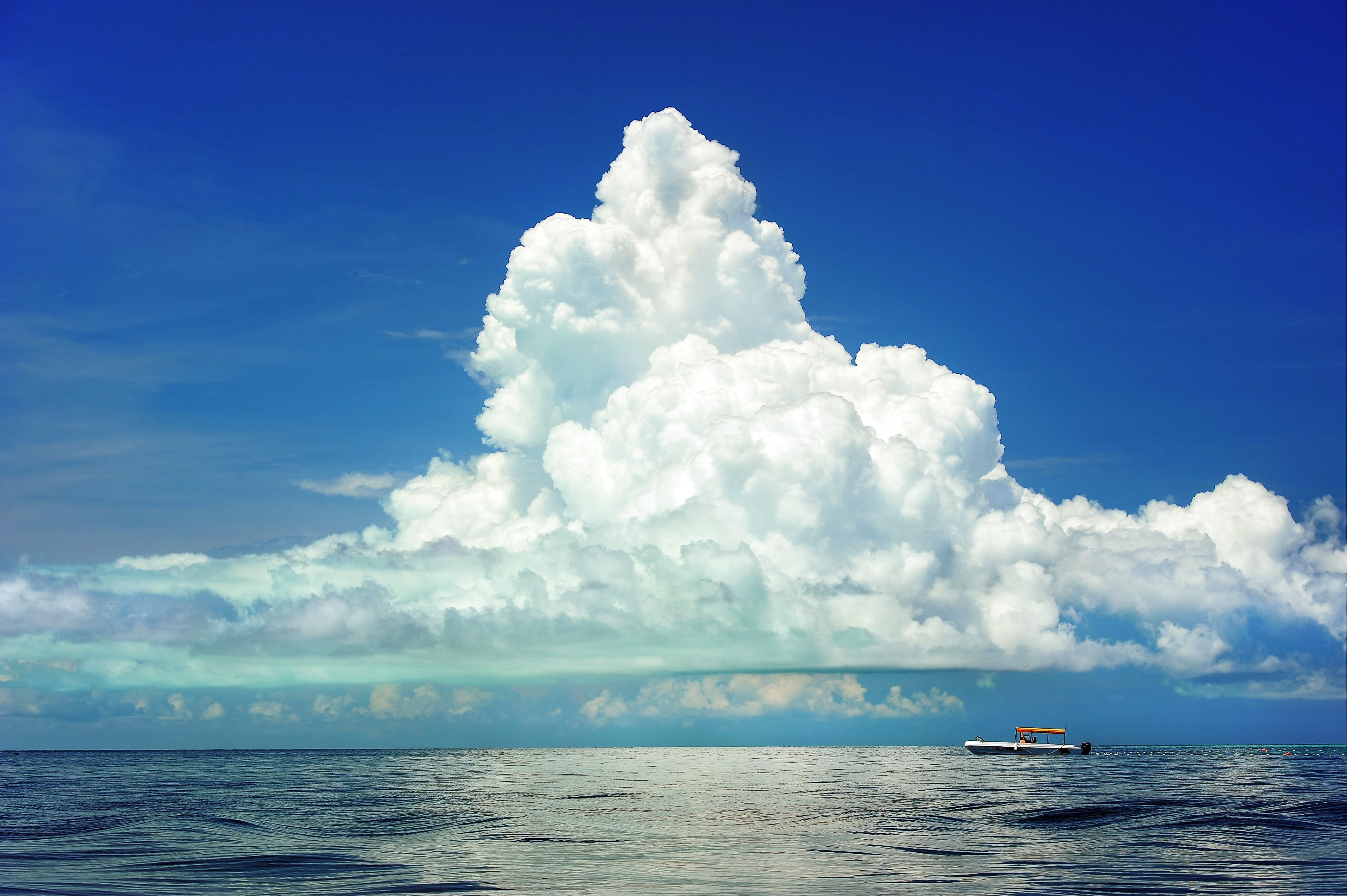 White Boat on Body of Water Under Cloudy Sky during Daytime
