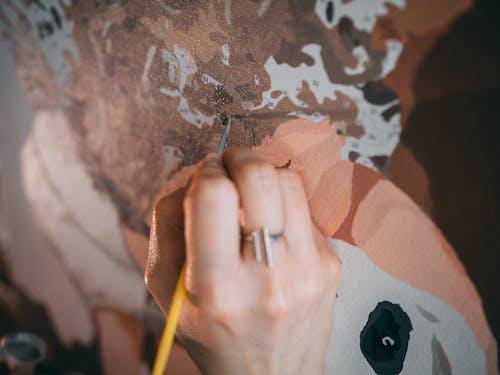 Anonymous female artist painting in studio