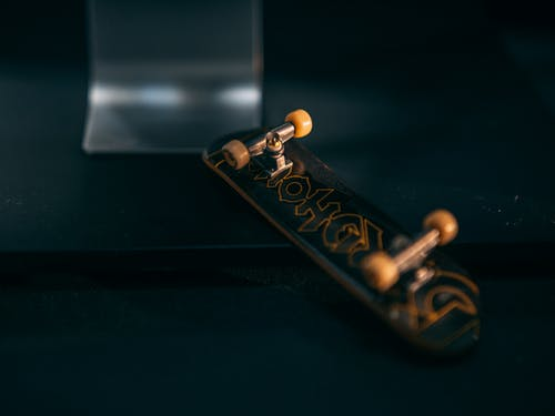 Stylish fingerboard near mini ramp on black table