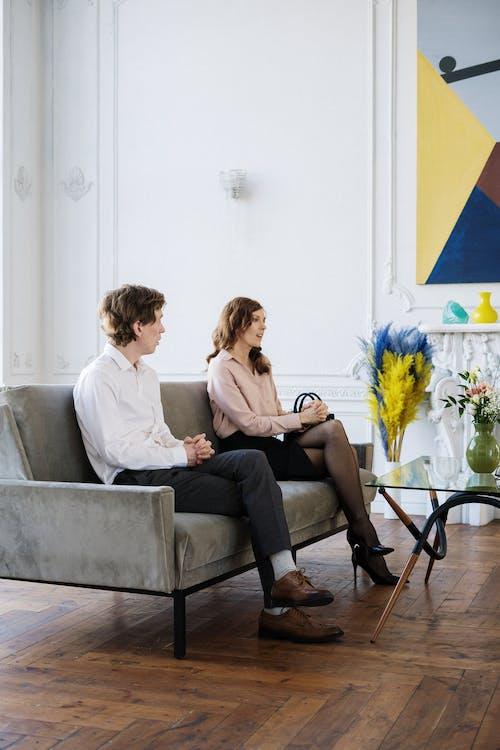 2 Women Sitting on Gray Sofa