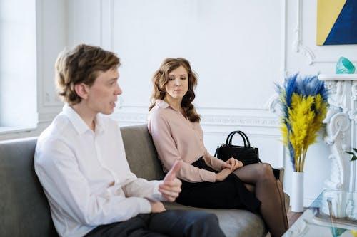 Woman in Black Dress Sitting Beside Man in White Suit