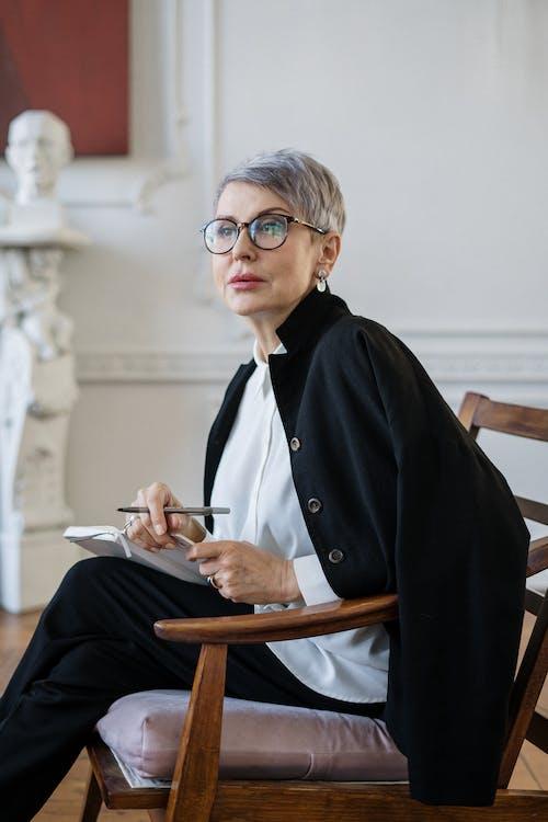 Woman in Black Blazer Sitting on Brown Wooden Chair