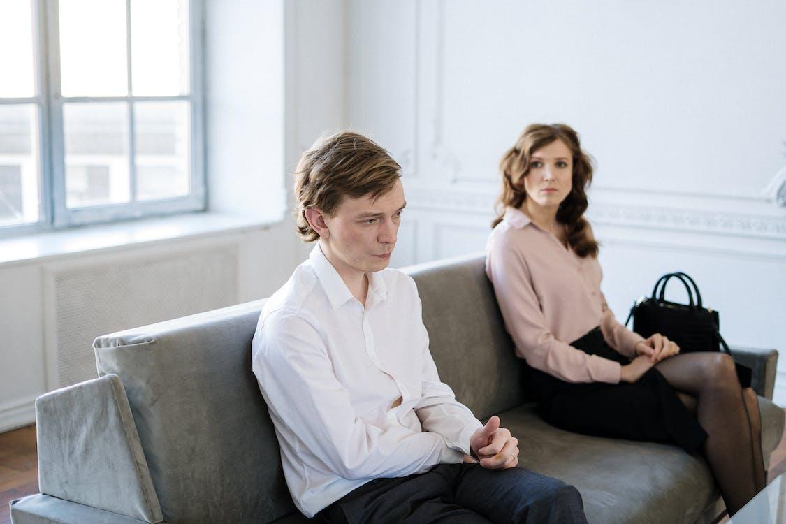 Man in White Suit Sitting Beside Woman in Black Dress