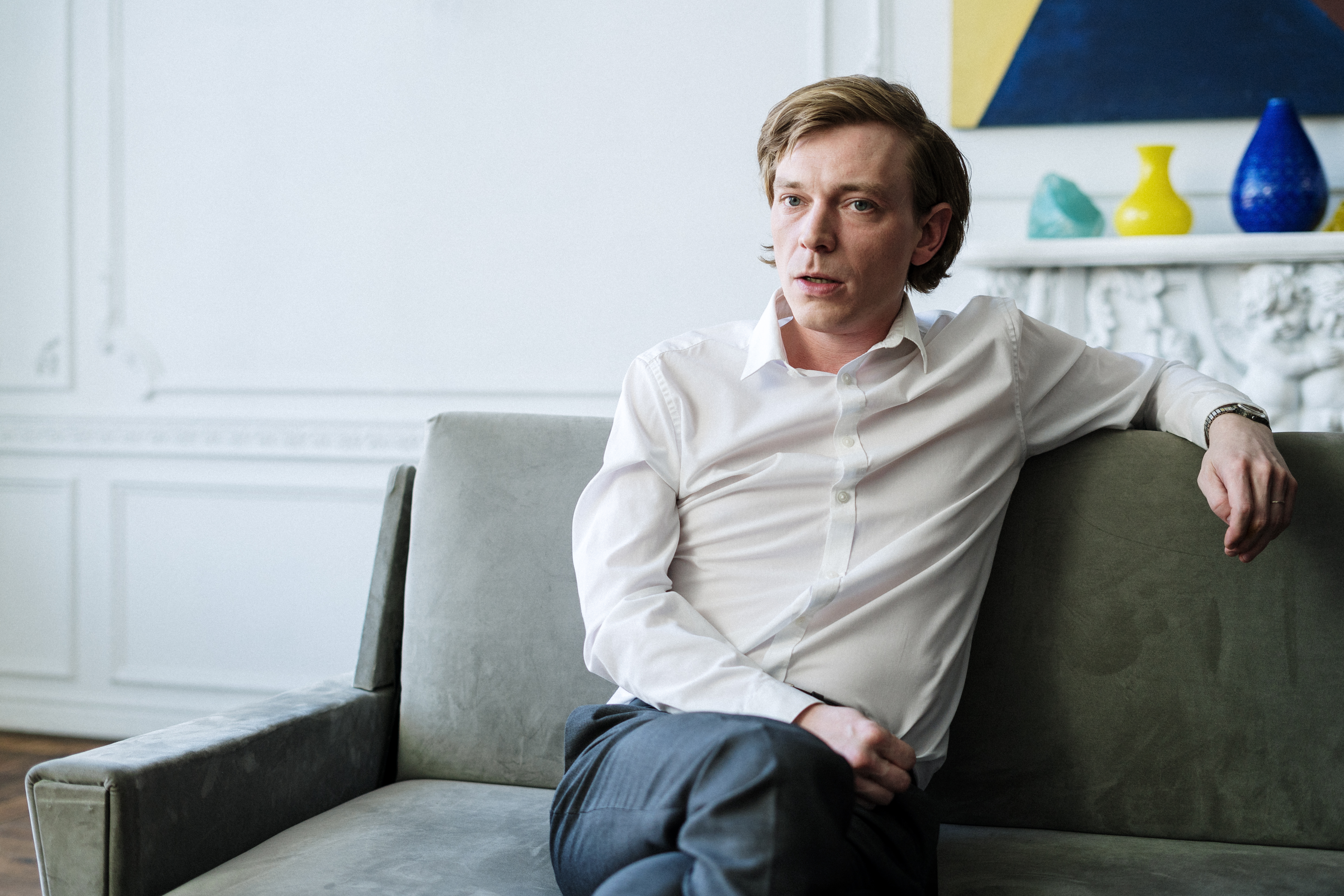man in white dress shirt sitting on gray couch