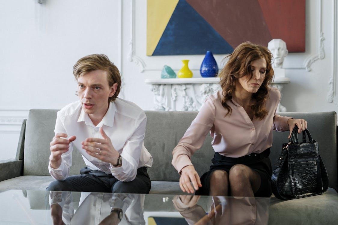 Woman in White Long Sleeve Shirt Sitting Beside Man in Gray Dress Shirt