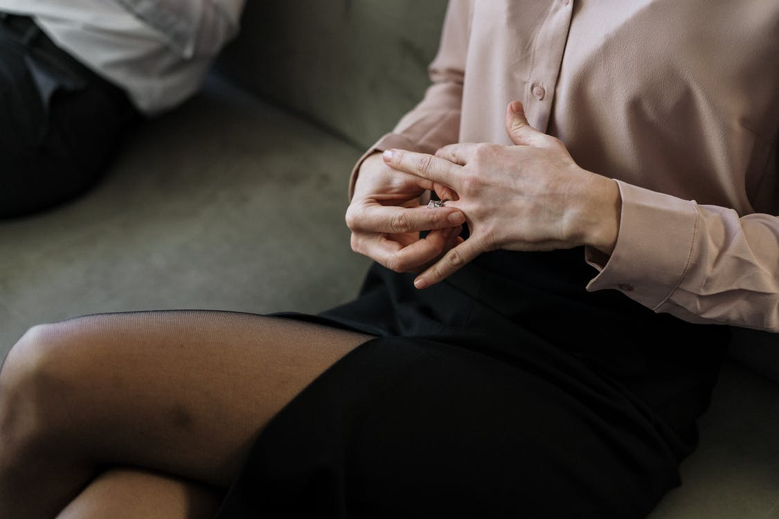 Person in White Button Up Shirt and Black Skirt Sitting on Gray Couch
