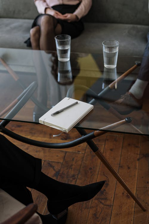 White and Silver Chair Beside Clear Drinking Glass on Glass Table