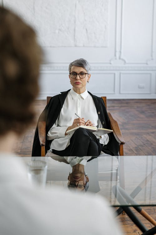 Woman in Black Blazer and White Dress Sitting on Chair