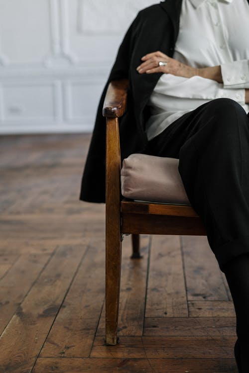Woman in White Long Sleeve Shirt and Black Pants Sitting on Brown Wooden Armchair