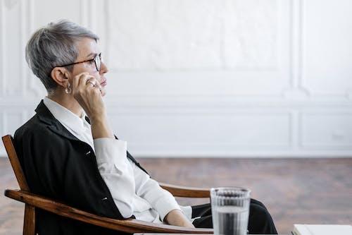 Man in White Dress Shirt Wearing Eyeglasses Sitting on Chair