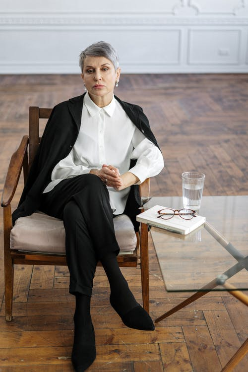 Man in White Dress Shirt and Black Dress Pants Sitting on Brown Wooden Chair