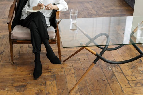 Woman in White Long Sleeve Shirt and Black Pants Sitting on Brown Wooden Chair