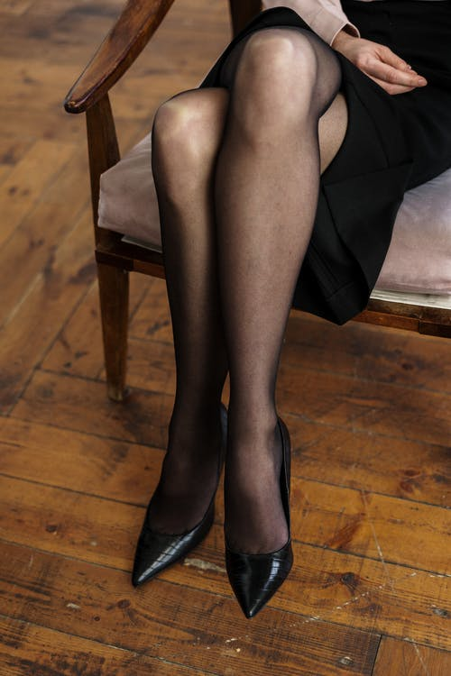 Woman in Black Stockings and Black Leather Heeled Shoes Sitting on Brown Wooden Chair