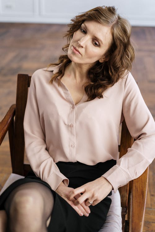 Woman in White Dress Shirt and Black Pants Sitting on Brown Wooden Chair