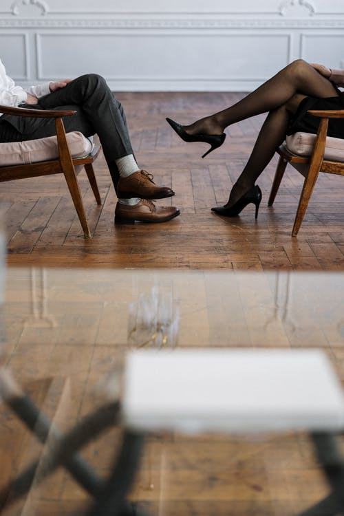 Person in Black Leather Heeled Shoes Sitting on Brown Wooden Chair