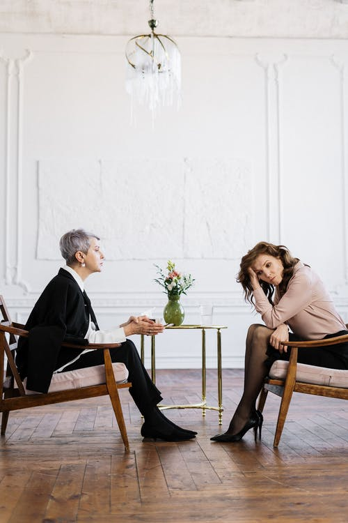 Man and Woman Sitting on Brown Wooden Chair