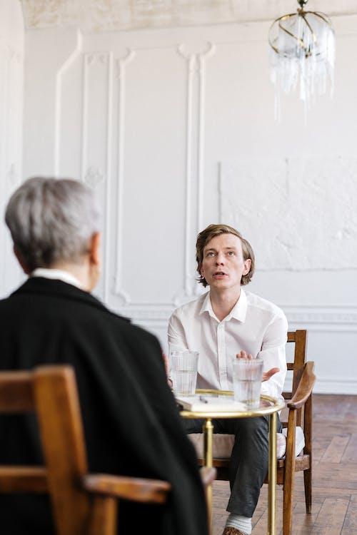 Man in Black Suit Sitting Beside Woman in White Dress Shirt