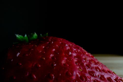 High angle closeup of fresh ripe juicy strawberry placed on table against black background