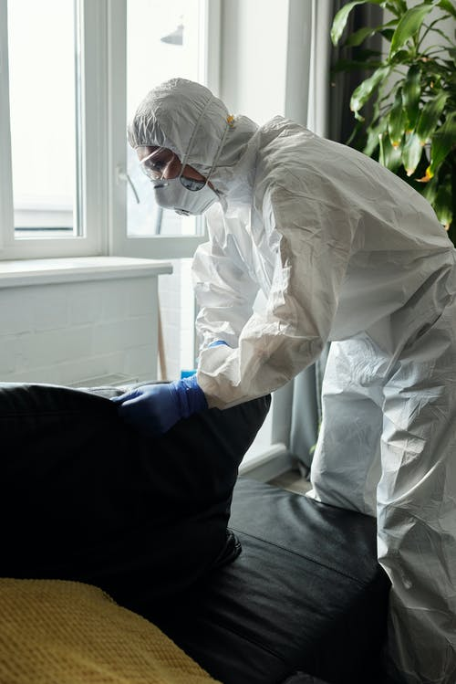 Person Wearing White PPE while Cleaning the Couch