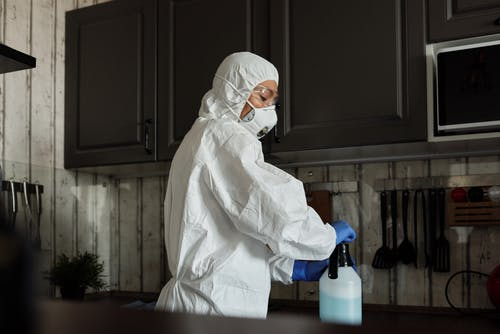 Person in White PPE Closing the Spray Bottle