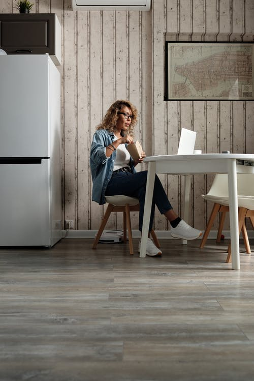 Woman in Blue Denim Jacket Sitting Using A Laptop While Eating