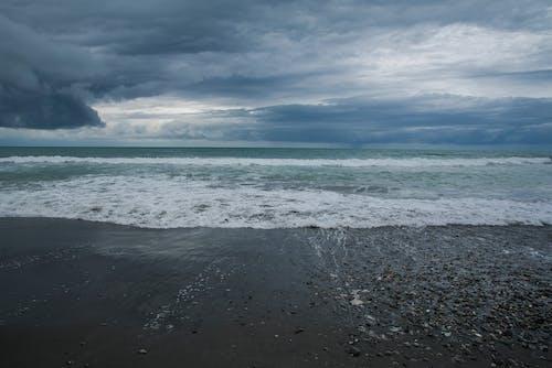 Sea Waves Crashing on Shore Under Cloudy Sky