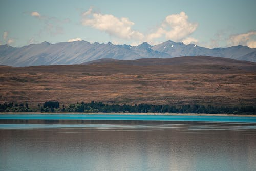 Brown and Gray Mountains Near Body of Water