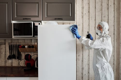 Person in Protective Suit Disinfecting A Refrigerator