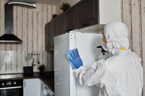 Person In A Protective Suit Disinfecting Inside The House