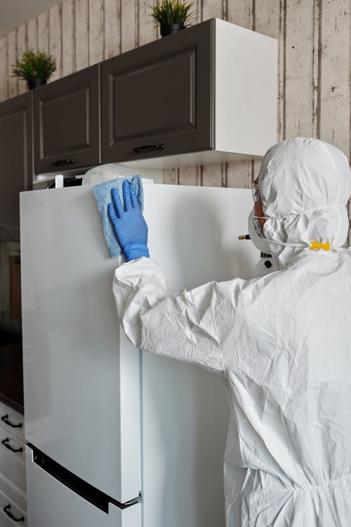 Person in Protective Suit Disinfecting The House