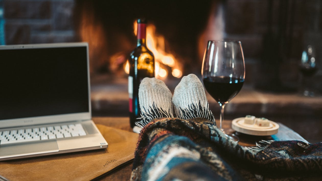 Macbook Pro Beside Wine Glass on Brown Wooden Table