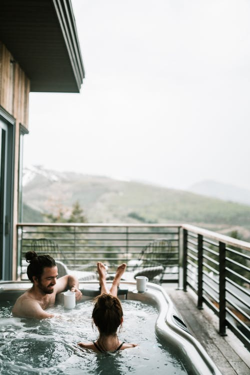 A Couple In A Jacuzzi In A Balcony