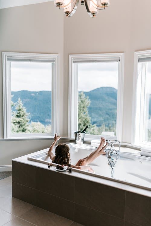 Woman in Bathtub Looking at the Window