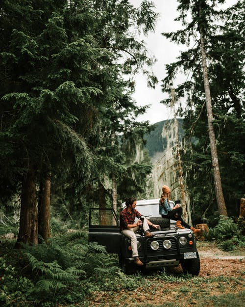 Man and Woman Sitting on Black Jeep Wrangler