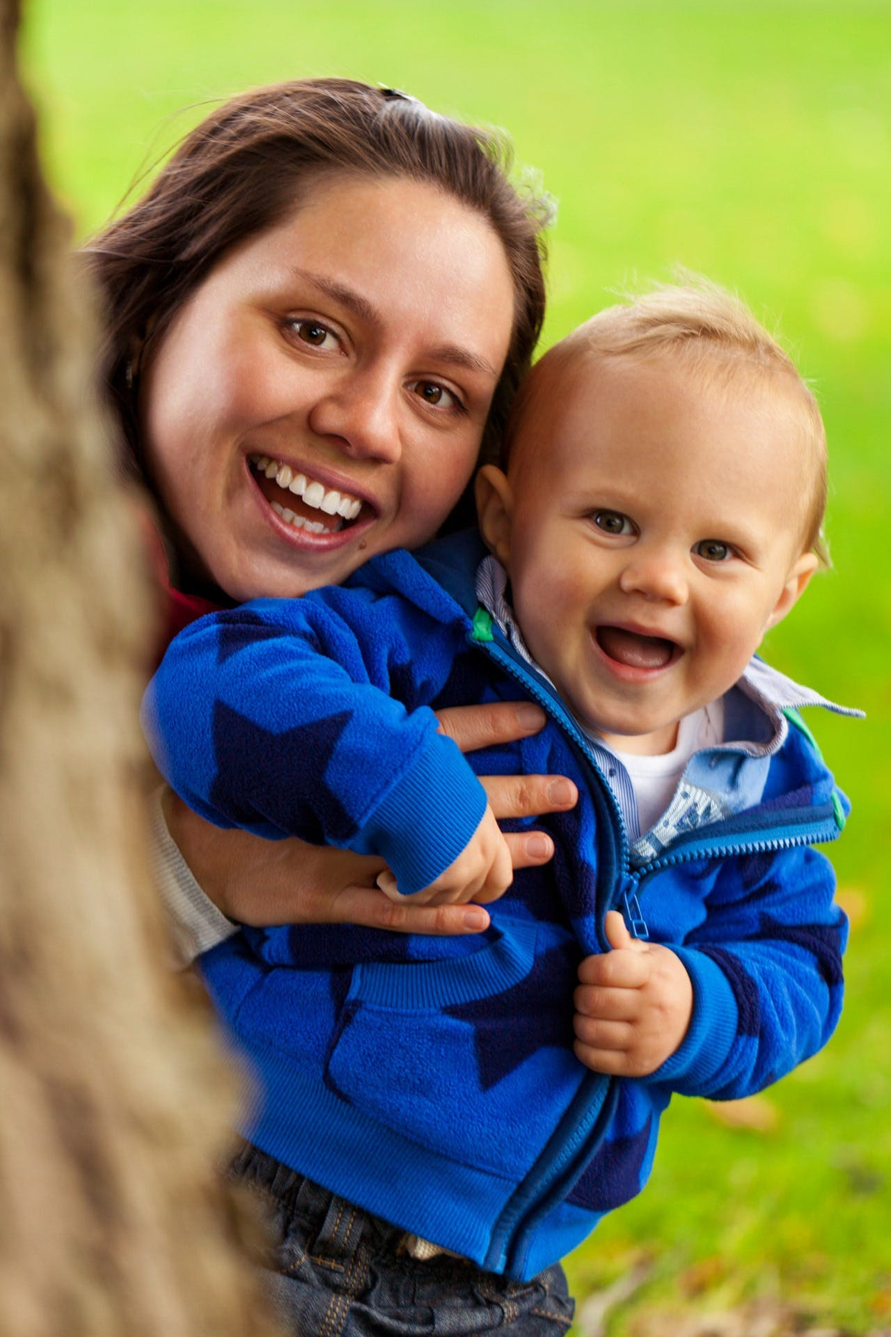 Smiling Woman Carrying Smiling Child Behind Tree Trunk