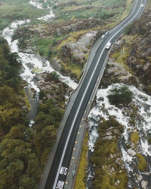 Asphalt road through rocky terrain and river