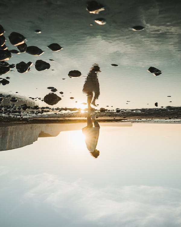 Upside down of anonymous person standing alone and reflecting in water surface during sunset