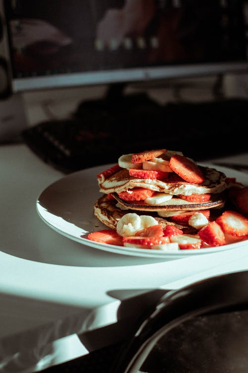 Pancakes With Slices Of Banana And Strawberry on White Ceramic Plate