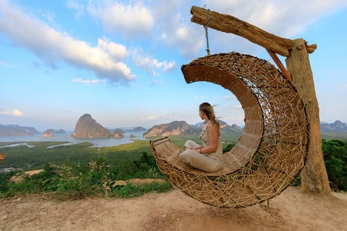 Woman in White Shirt Sitting on Brown Woven Hammock