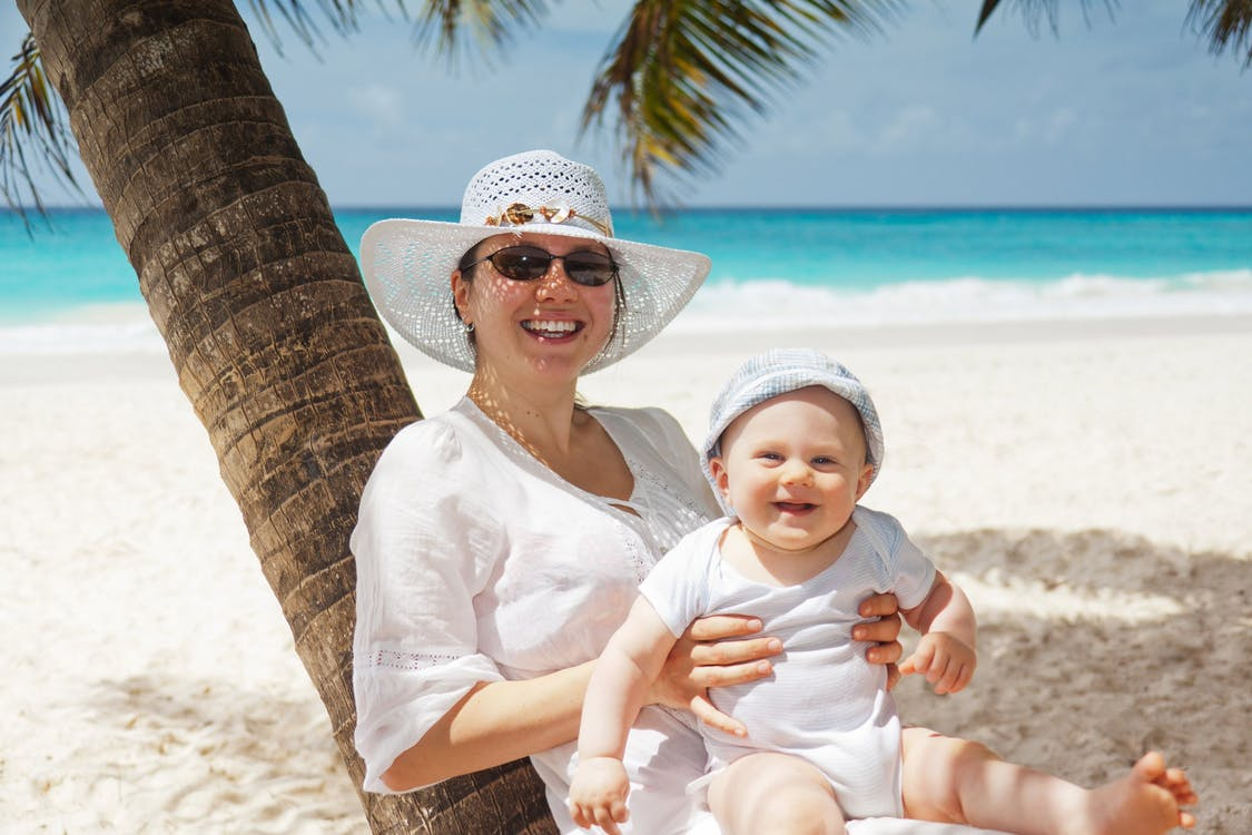 Woman Holding Infant on Beach