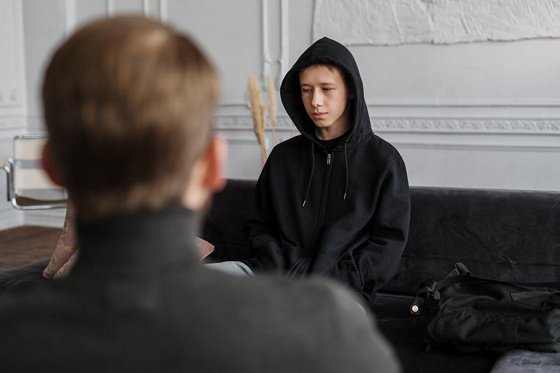 Man in Black Hoodie Sitting Beside Boy in Black Hoodie
