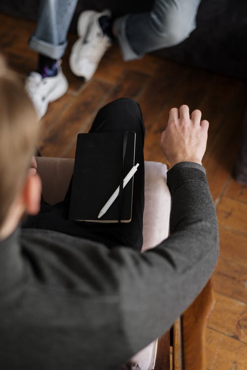 Person in Gray Long Sleeve Shirt Holding Black Tablet Computer