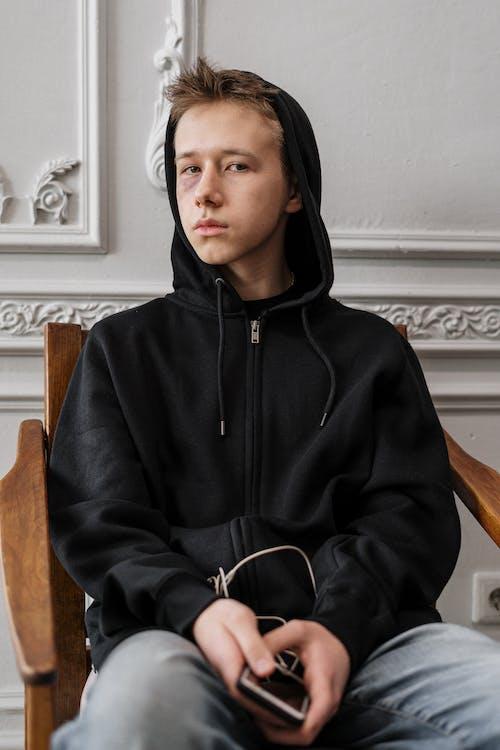 Man in Black Hoodie Sitting on Brown Wooden Chair