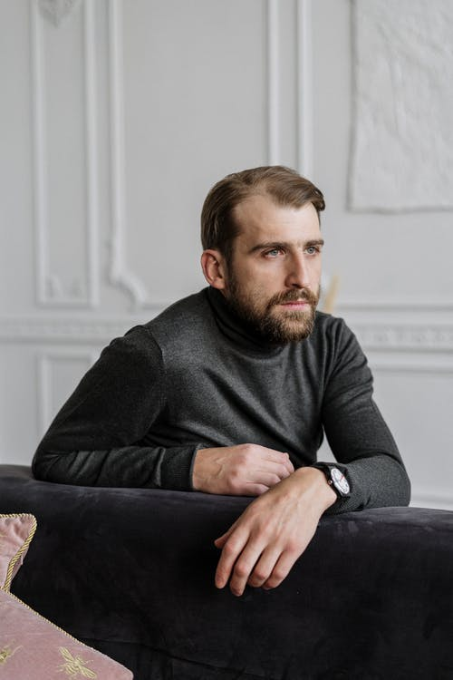 Man in Black Sweater Sitting on Black Couch